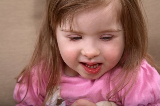 Portrait of little handicapped caucasian girl with Down Syndrome
