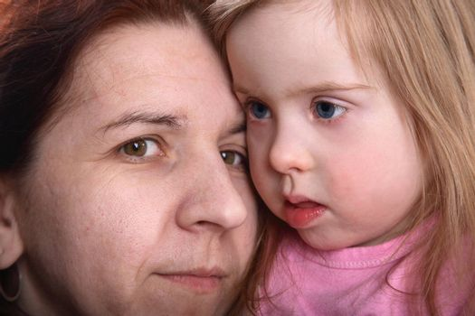 A closeup portrait of a young girl with Down Syndrome and her mother.