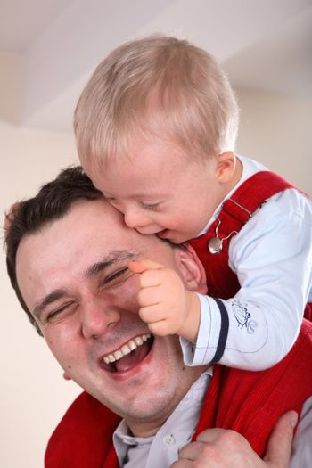 Laughing father with his young handicapped son sitting on his shoulders.