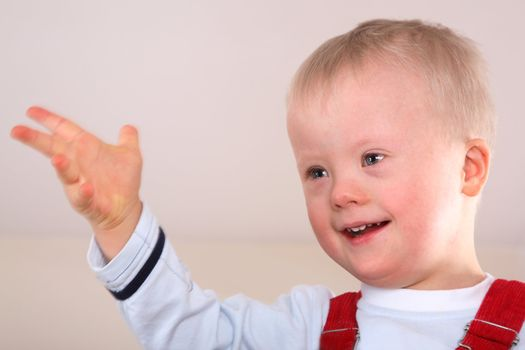 Portrait of a handicapped caucasian happy smiling boy with Down Syndrome.