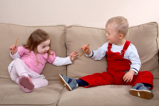 A little boy and girl with Down syndrome sitting on a sofa.