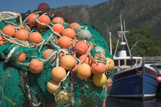 Fishing nets with bright orange floats in a dock; fishing boat in the background; background not in focus.