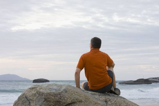 Man sitting on a rock contemplating the sea