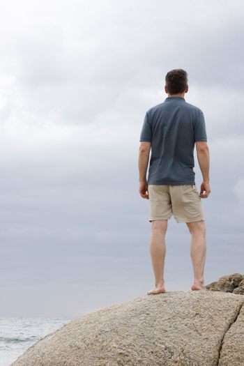 Man standing barefoot on a rock at the sea
