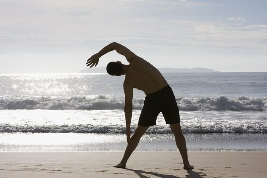 Man doing exercises on a beach at sunrise