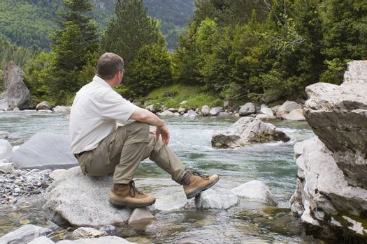 Hiker sitting at a mountain creek. National park Ordesa y Monte perdido - Spain
