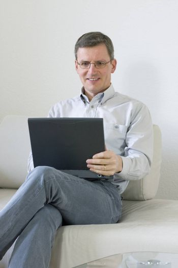 Middle-aged man at home sitting on a couch with laptop computer