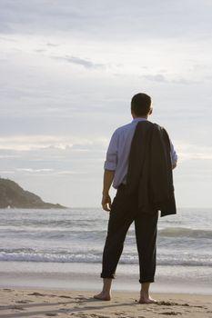 Businessman relaxing barefoot on a beach