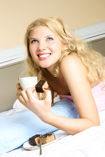 happy beautiful blond girl drinking tea with a cake in her bed at home