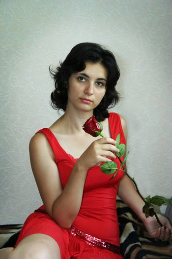 The beautiful girl holds a scarlet rose
