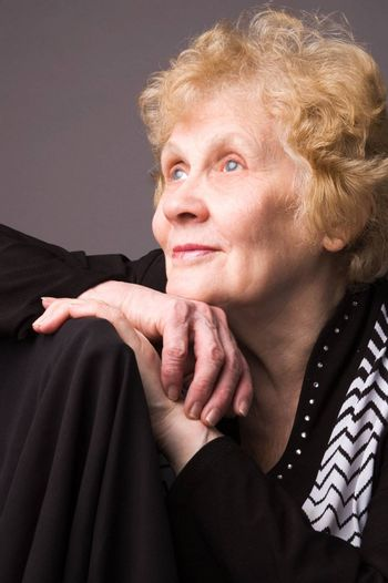 The elderly woman in a black dress on a grey background.