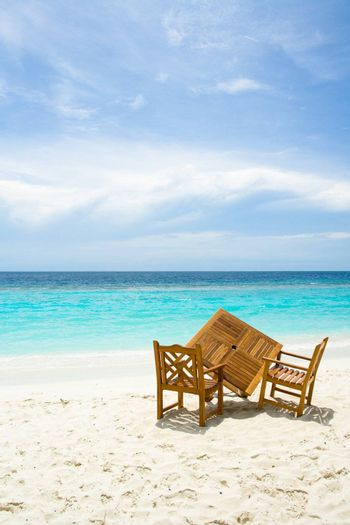 Wooden table and chairs on the sandy beach with ocean view