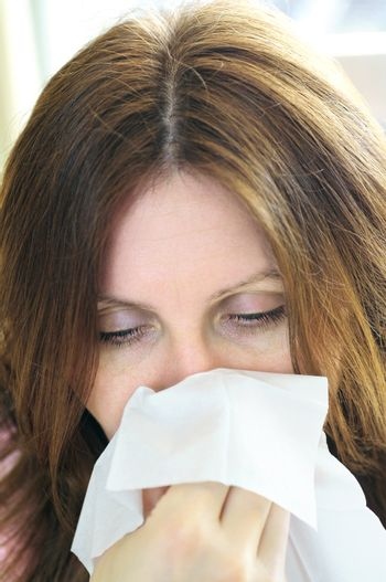 Mature woman with a flu or an allergy symptoms