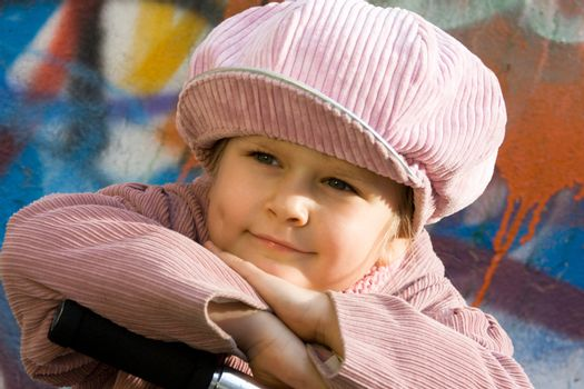 Portrait of happy little girl who is taking a respite near graffiti painted wall