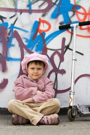 Funny little girl with scooter is sitting on the ground near graffiti painted wall