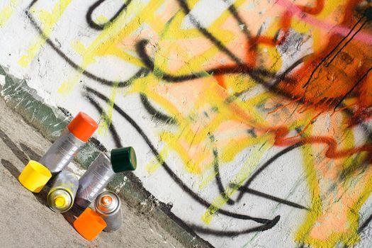 Aerosol paint on the ground near graffiti painted wall