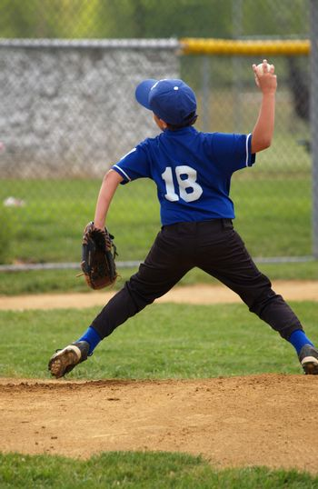 little league baseball pitcher throwing the ball from the mound
