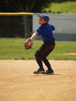 little league baseball player throwing the baseball