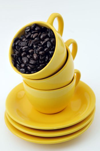 Three yellow cups full with coffe beans isolated on white