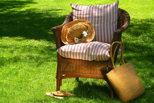 Straw hat, old wicker chair waiting for someone to relax on a hot summer's day