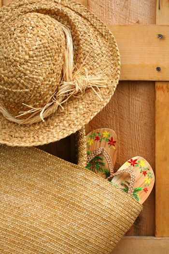 Pair of sandals hanging out of wicker purse with sun hat