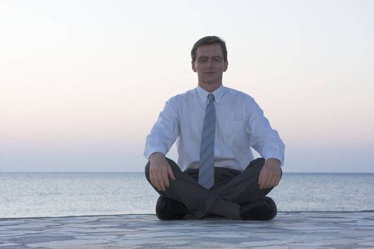 Businessman meditating by the sea at sunrise