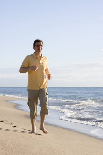 Man running on the beach at in the morning