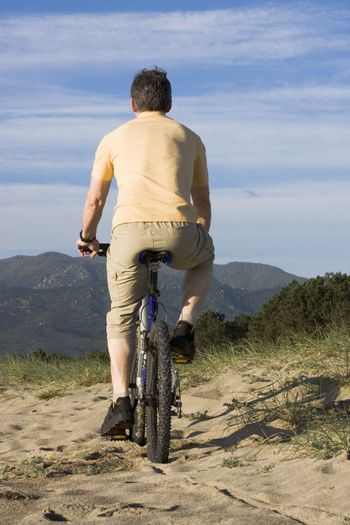 Man riding bicycle on the beach with hills in the background