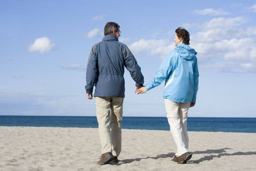 Mid-adult couple walking hand in hand on the beach