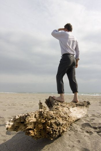 Shipwrecked businessman standing on a tree trunk on a beach
