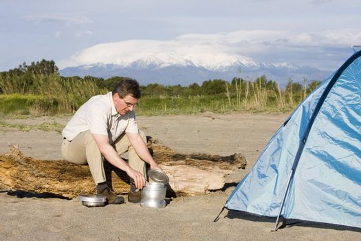Man cooking beside his tent in front of a mountain with snow