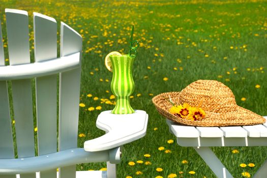 Adirondack chair on the grass with cool summer drink