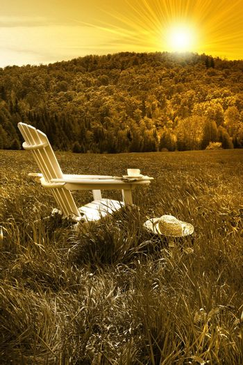 Relaxing on a summer chair in a field of tall grass at sunset