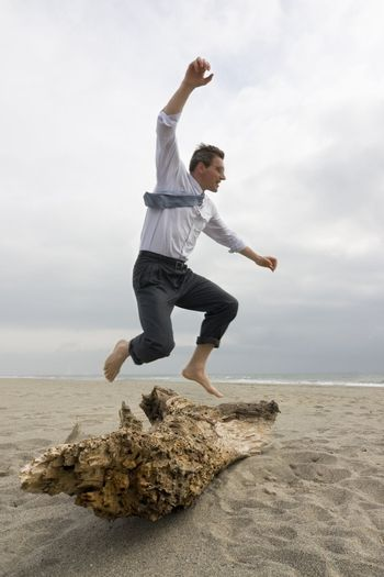 Businessman jumping over a tree trunk on a beach