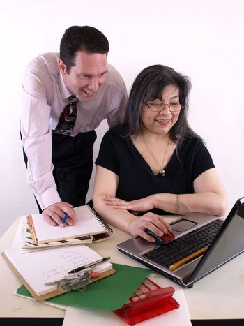 A male and female working together in the office at the computer. Isolated against a white background.