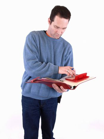 An adult male in blue checks over some figures in a binder. Isolated on a white background.