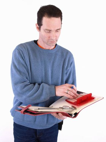 An adult male in blue checks over some measurements in a binder. Isolated on a white background.
