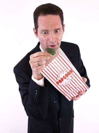 A man in a black suit pulls a piece of broccoli from a popcorn bag. Over white.