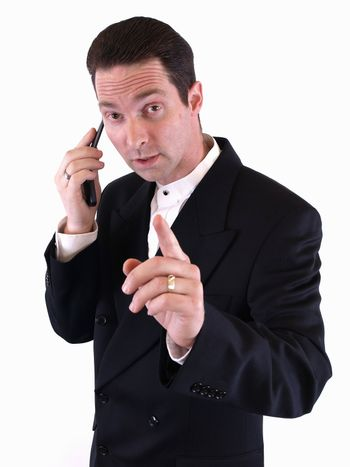 A man in a black suit holds up his finger to signal he is busy and on the telephone.
