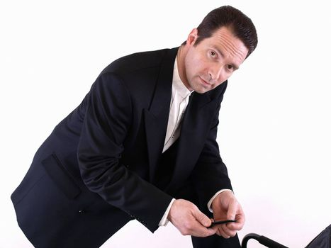 A standing man leans down on one knee to check an incoming text message on his cell phone.