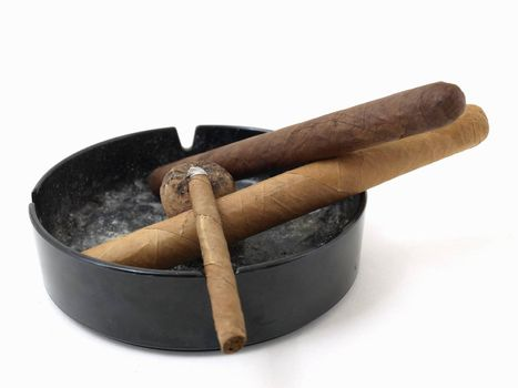 Three cigars resting in a dirty ashtray isolated on a white background.