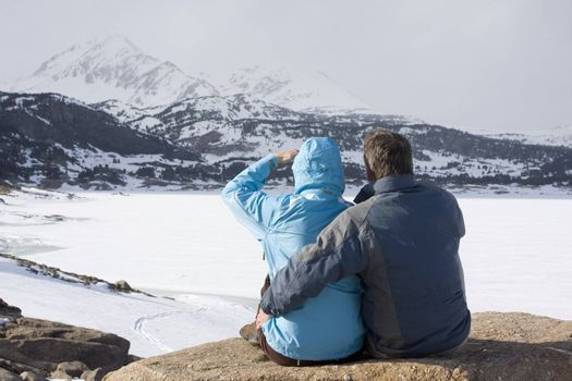 Couple sitting in front of mountains with snow and ice