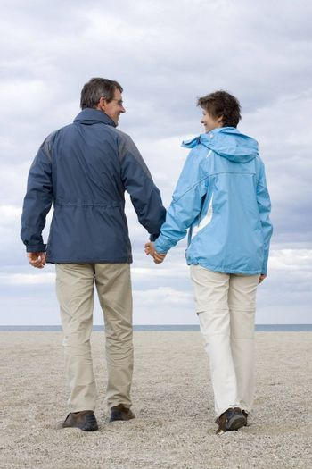 Smiling mature couple walking hand in hand on a beach