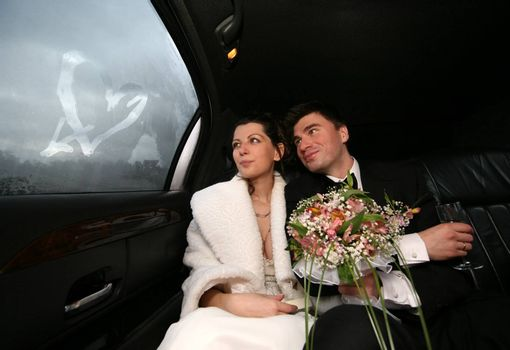 The bride and groom in automobile