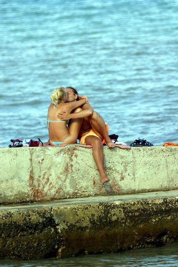 The man and the woman kiss on a pier