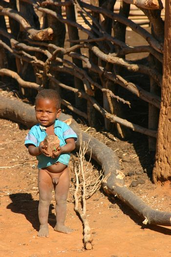 Young boy in a Malagassy village playing with a rock