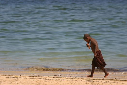 Young boy walking along the beach at Ifaty