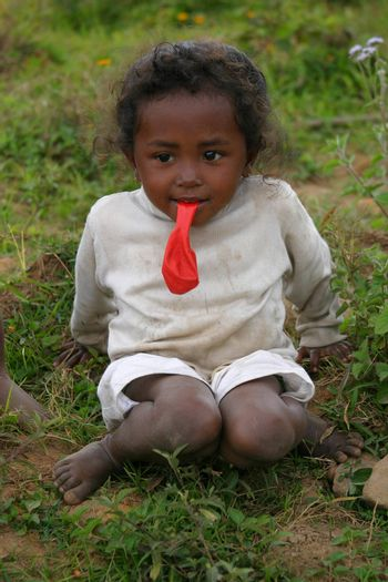 Little child sitting by the site of the road with a balloon in her mouth in Madagascar