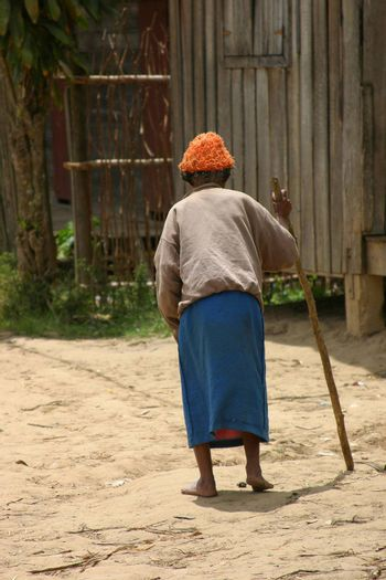 Elderly woman shuffling along the road leaning on a cane in Madagascar