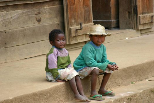 Two kids in Madagascar spending the time watching the world go by